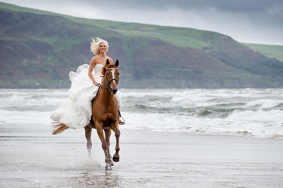 Bride on horse back, Bride riding horse on the beach.